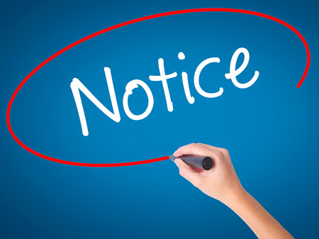 importance: Women Hand writing Notice with black marker on visual screen. Isolated on blue. Business, technology, internet concept. Stock Photo
