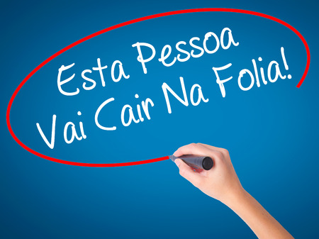 Women Hand writing Esta Pessoa Vai Cair Na Folia! (This Person Will be at Carnaval in Portuguese) with black marker on visual screen. Isolated on blue. Business, technology, internet concept. Stock Photo Imagens