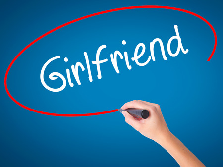 severance: Women Hand writing Girlfriend with black marker on visual screen. Isolated on blue. Business, technology, internet concept.