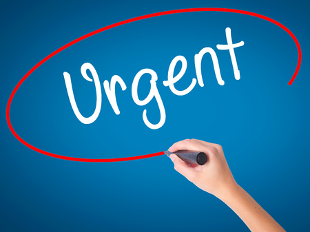 Women Hand writing Urgent  with black marker on visual screen. Isolated on blue. Business, technology, internet concept. Stock  Photo