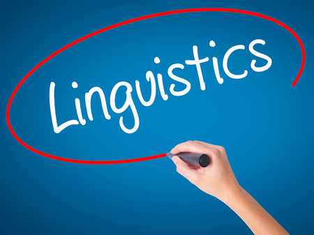 Women Hand writing Linguistics  with black marker on visual screen. Isolated on blue. Business,  technology, internet concept. Stock Photo