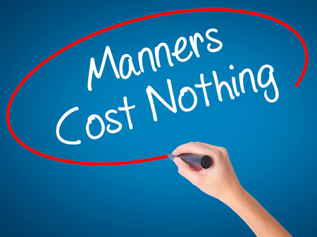 Women Hand writing Manners Cost Nothing with black marker on visual screen. Isolated on blue. Business, technology, internet concept. Stock Photo