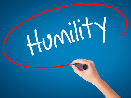 humility: Women Hand writing Humility  with black marker on visual screen. Isolated on blue. Business, technology, internet concept. Stock Photo