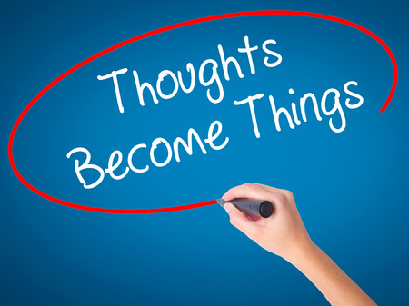 mental object: Women Hand writing Thoughts Become Things with black marker on visual screen. Isolated on blue. Business, technology, internet concept. Stock Photo Stock Photo