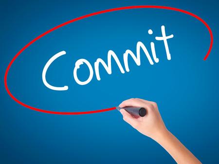 comité d entreprise: Femmes Hand Writing Commit avec un marqueur noir sur l'écran visuel. Isolé sur le bleu. Affaires, technologie, internet concept. photo Banque d'images
