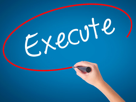 execute: Women Hand writing Execute with black marker on visual screen. Isolated on blue. Business, technology, internet concept. Stock Photo