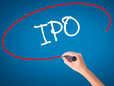 valued: Women Hand writing IPO (Initial Public Offering)   with black marker on visual screen. Isolated on blue. Business, technology, internet concept. Stock Photo
