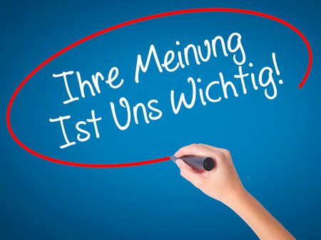 Women Hand writing Ihre Meinung Ist Uns Wichtig! (Your Opinion is Important to Us in German) with marker on visual screen. Isolated on blue. Business, technology, internet concept. Stock Photo