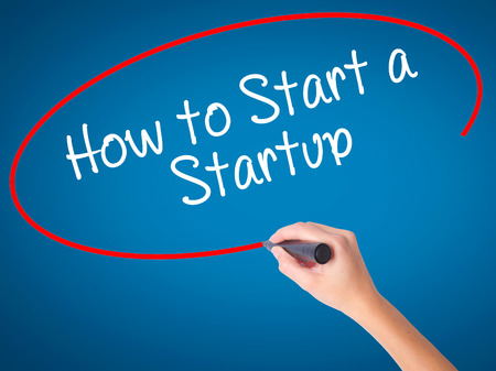 Women Hand writing How to Start a Startup with black marker on visual screen. Isolated on blue. Business, technology, internet concept. Stock Photo