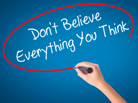 Women Hand writing Dont Believe Everything You Think with black marker on visual screen. Isolated on blue. Business, technology, internet concept. Stock Photo Stock Photo
