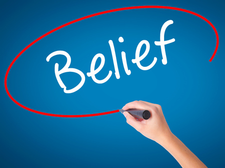 posit: Women Hand writing Belief with black marker on visual screen. Isolated on blue. Business, technology, internet concept. Stock Photo
