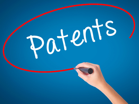 patents: Women Hand writing Patents with black marker on visual screen. Isolated on blue. Business, technology, internet concept. Stock Photo