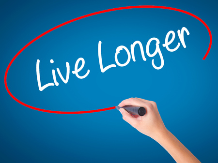 longevity medicine: Women Hand writing Live Longer with black marker on visual screen. Isolated on blue. Business, technology, internet concept. Stock Photo Stock Photo