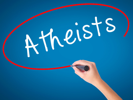 disbelieve: Women Hand writing Atheists with black marker on visual screen. Isolated on blue. Business, technology, internet concept. Stock Image Stock Photo