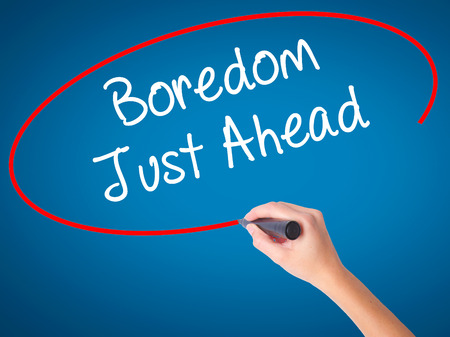 Women Hand writing Boredom Just Ahead with black marker on visual screen. Isolated on blue. Business, technology, internet concept. Stock Photo