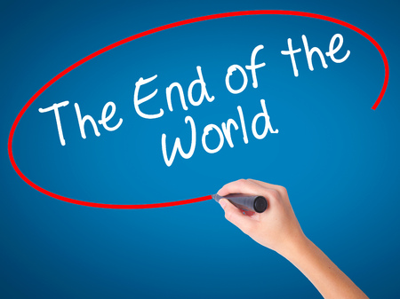 end of world: Women Hand writing The End of the World with black marker on visual screen. Isolated on blue. Business, technology, internet concept. Stock Photo