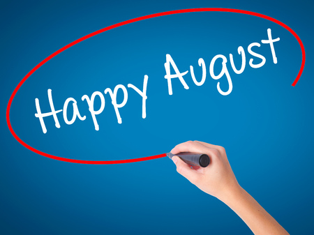 Women Hand writing Happy August with black marker on visual screen. Isolated on blue. Business, technology, internet concept. Stock Photo