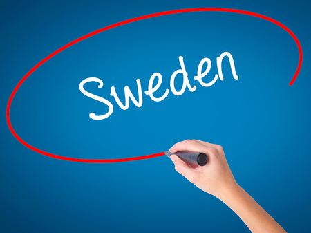 sweden winter: Women Hand writing Sweden  with black marker on visual screen. Isolated on blue. Business, technology, internet concept.
