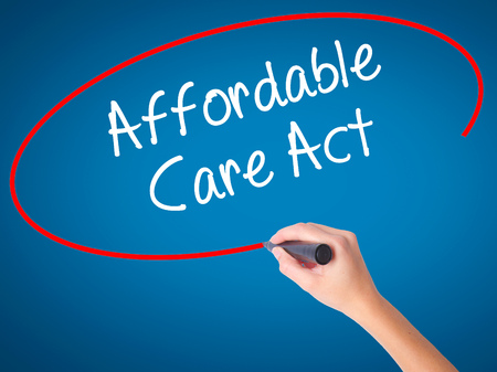 affordable: Women Hand writing Affordable Care Act with black marker on visual screen. Isolated on blue. Business, technology, internet concept. Stock Photo