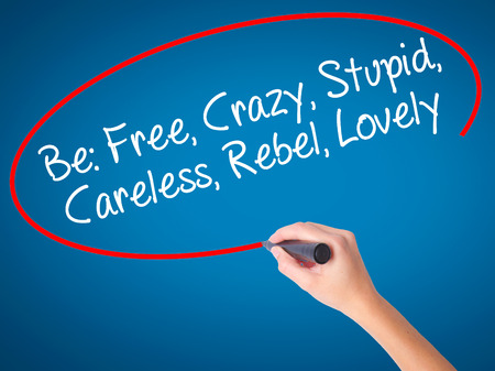 careless: Women Hand writing Be: Free, Crazy, Stupid, Careless, Rebel, Lovely with black marker on visual screen. Isolated on blue. Business, technology, internet concept. Stock Photo Stock Photo