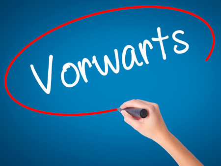 Women Hand writing Vorw??¤rts  (Forward In German)  with black marker on visual screen. Isolated on blue. Business, technology, internet concept. Stock Photo