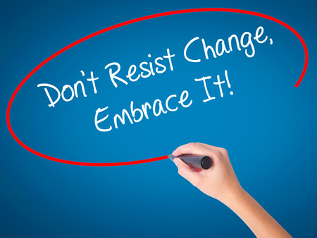 Women Hand writing Dont Resist Change, Embrace It! with black marker on visual screen. Isolated on blue. Business, technology, internet concept.
