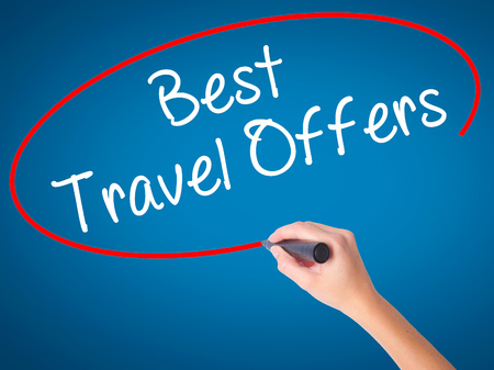 Women Hand writing Best Travel Offers  with black marker on visual screen. Isolated on blue. Travel technology, internet concept. Stock Image