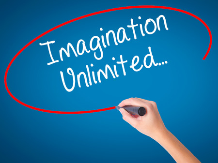 Women Hand writing Imagination Unlimited... with black marker on visual screen. Isolated on blue. Business, technology, internet concept. Stock Photo