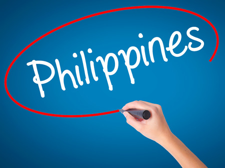 Women Hand writing Philippines with black marker on visual screen. Isolated on blue. Business, technology, internet concept. Stock Photo