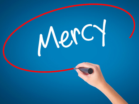 mercy: Women Hand writing Mercy with black marker on visual screen. Isolated on blue. Business, technology, internet concept. Stock Photo