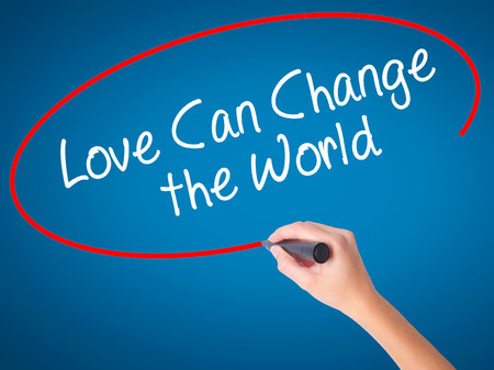 Women Hand writing Love Can Change the World with black marker on visual screen. Isolated on blue. Business, technology, internet concept. Stock Photo Stock Photo