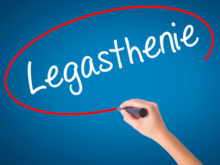 reversing: Women Hand writing Legasthenie (Dyslexia in German) with black marker on visual screen. Isolated on blue. Business, technology, internet concept. Stock Photo