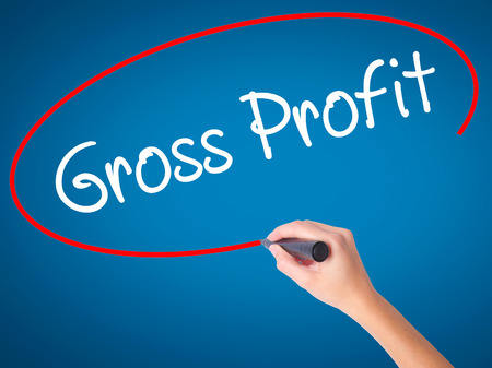 Women Hand writing Gross Profit with black marker on visual screen. Isolated on blue. Business, technology, internet concept. Stock Photo Stock Photo