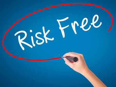 Women Hand writing Risk Free with black marker on visual screen. Isolated on blue. Business, technology, internet concept. Stock Image