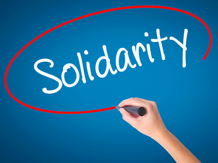 Women Hand writing Solidarity  with black marker on visual screen. Isolated on blue. Business, technology, internet concept. Stock Photo