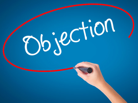 objection: Women Hand writing Objection with black marker on visual screen. Isolated on blue. Business, technology, internet concept. Stock Photo