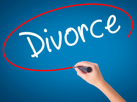 Women Hand writing Divorce  with black marker on visual screen. Isolated on blue. Business, technology, internet concept. Stock Photo