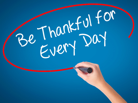 Women Hand writing Be Thankful for Every Day   with black marker on visual screen. Isolated on blue. Business, technology, internet concept. Stock Photo