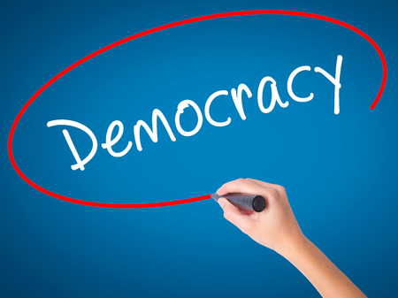 Women Hand writing Democracy with black marker on visual screen. Isolated on blue. Business, technology, internet concept. Stock Image Stock Photo