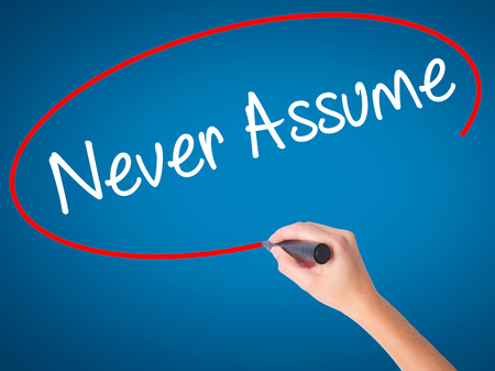 assume: Women Hand writing Never Assume with black marker on visual screen. Isolated on blue. Business, technology, internet concept. Stock Photo