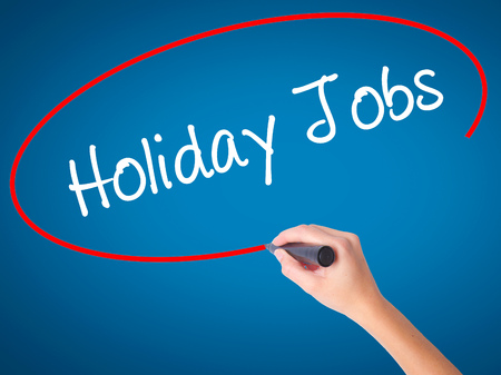 Women Hand writing Holiday Jobs  with black marker on visual screen. Isolated on blue. Business, technology, internet concept. Stock Photo