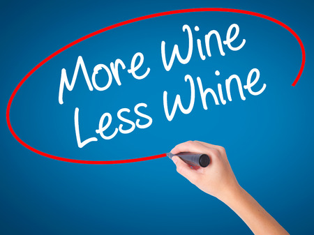 whine: Women Hand writing More Wine Less Whine with black marker on visual screen. Isolated on blue. Business, technology, internet concept. Stock Photo