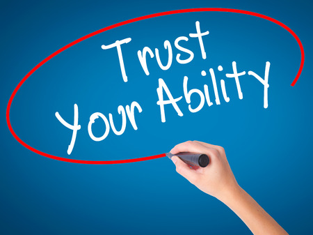 Women Hand writing Trust Your Ability  with black marker on visual screen. Isolated on blue. Business, technology, internet concept. Stock Photo