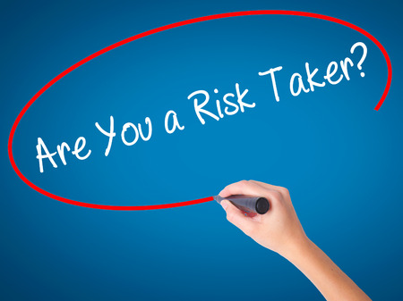 taker: Women Hand writing Are You a Risk Taker? with black marker on visual screen. Isolated on blue. Business, technology, internet concept. Stock Photo Stock Photo