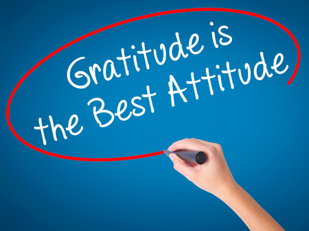 Women Hand writing Gratitude is the Best Attitude with black marker on visual screen. Isolated on blue. Business, technology, internet concept. Stock Photo Stock Photo