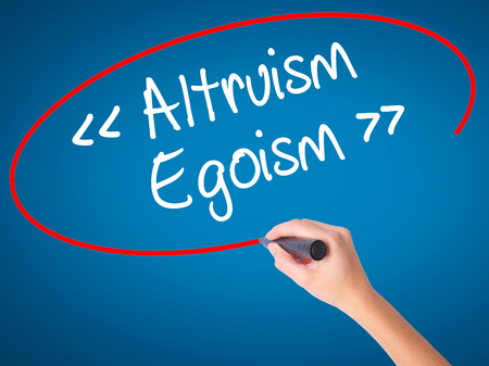 Women Hand writing Altruism - Egoism with black marker on visual screen. Isolated on blue. Business, technology, internet concept. Stock Photo