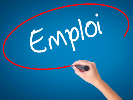 Women Hand writing Emploi (Employment in French) with black marker on visual screen. Isolated on blue. Business, technology, internet concept. Stock Photo