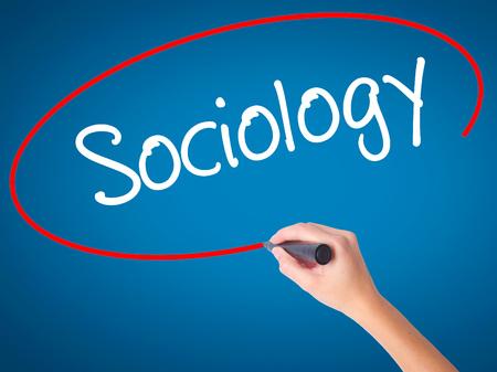 sociologia: Mujeres mano escribiendo Sociología con marcador negro en la pantalla visual. Aislado en azul. Negocios, la tecnología, el concepto de internet. Foto de stock Foto de archivo