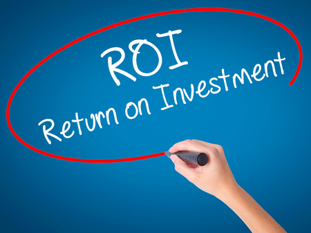 Women Hand writing ROI  Return on Investment with black marker on visual screen. Isolated on blue. Business, technology, internet concept. Stock Photo