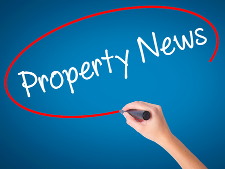 Women Hand writing Property News with black marker on visual screen. Isolated on blue. Business, technology, internet concept. Stock Photo